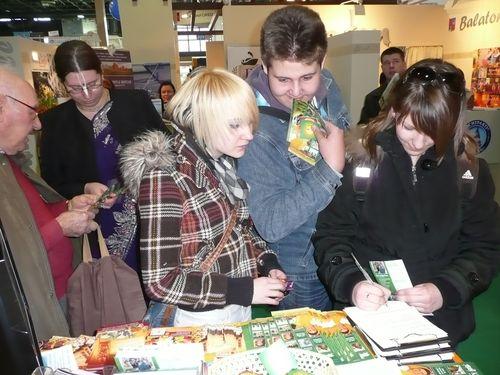 Látogatók regisztrálnak a nyereményjátékunkra a Krisna-völgyi standnál