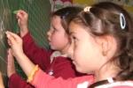 Betűvetést gyakorló gyerekek a Krisna-völgyi Általános Iskola táblájánál
